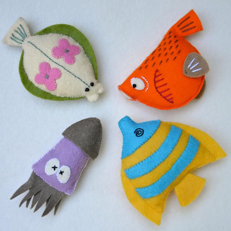 Cuatro peces realizados en fieltro y colocados  formando un círculo.